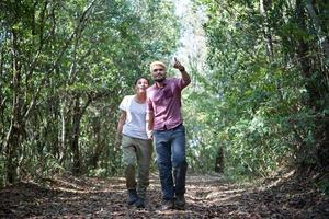 giovane coppia attraente escursioni nella foresta foto