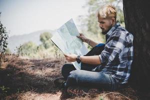 escursionista rilassante da una struttura ad albero guardando la mappa foto