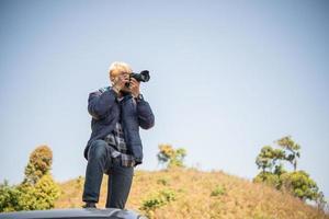 giovane fotografo seduto sul suo camioncino che fotografa una montagna foto