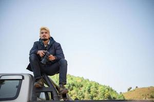 giovane fotografo seduto sul suo camioncino foto