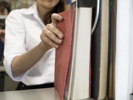 giovani studenti che trovano libri nella biblioteca universitaria foto
