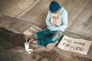 mendicanti seduti sotto il ponte con un segno