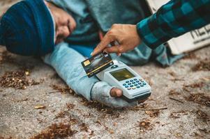 mendicante con una macchina magnetica per carte di credito foto