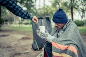 mendicante avvolto in stoffa in strada che accetta denaro foto