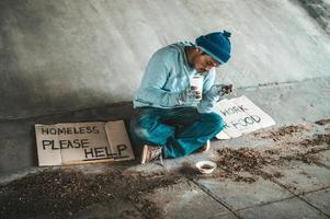 mendicante sotto il ponte con una tazza contenente monete e spaghetti istantanei foto