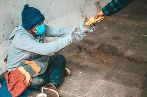 la macchina per il pane dà a un mendicante sul ciglio della strada foto