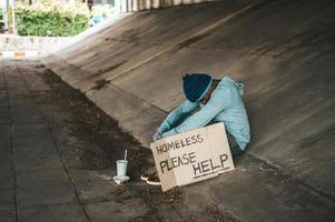 mendicante seduto sotto un ponte con una tazza di soldi e tagliatelle foto