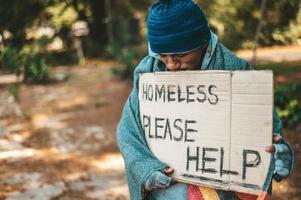 mendicante sta sulla strada con per favore aiuto segno foto