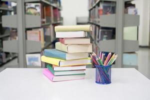 pila di libri e articoli di cancelleria in biblioteca foto