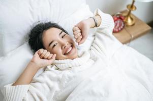 giovane donna che indossa una camicia bianca appena svegliarsi nel letto foto