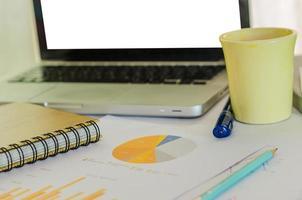 scrivania disordinata con grafici e caffè