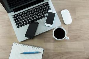laptop e smart phone su una scrivania foto