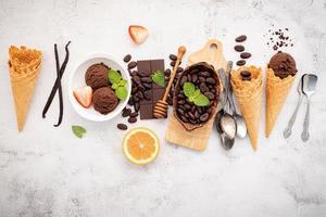 gusti di gelato al cioccolato in ciotola con cioccolato fondente foto