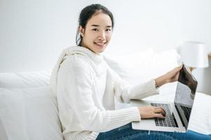 giovane donna che indossa una camicia bianca che gioca sul suo computer portatile foto