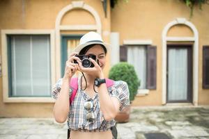 ritratto di donna piuttosto giovane hipster divertirsi in città con la fotocamera foto
