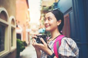 primo piano di una donna giovane hipster in viaggio e scattare foto con la sua macchina fotografica
