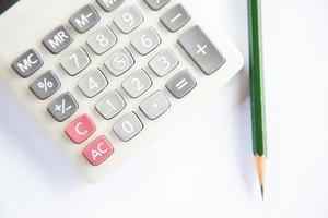 calcolatrice e matita sulla scrivania foto