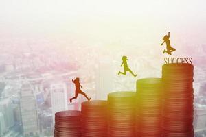 silhouette di persone che corrono su un mucchio di monete con lo sfondo della città foto