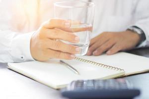 uomo d'affari tenendo un bicchiere di acqua potabile