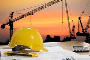 casco di sicurezza con oggetti di costruzione sul tavolo con paesaggio urbano foto