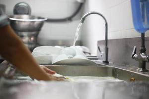 persona che lava il piatto nel lavandino foto