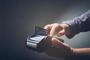 persona che utilizza una macchina per carte di credito foto