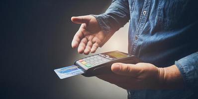 persona che paga con la macchina della carta di credito foto