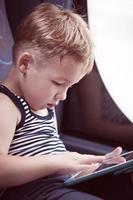 bambino che utilizza tablet durante il viaggio in autobus