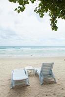 lettini prendisole bianchi sulla spiaggia foto