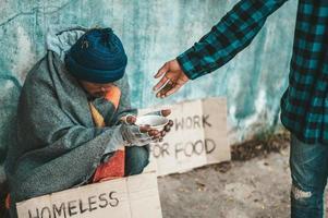 il panettiere dà a un mendicante sul ciglio della strada foto