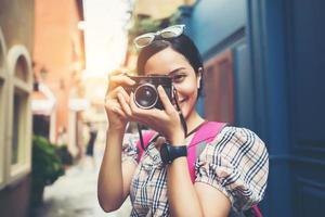 primo piano di una donna giovane hipster, zaino in spalla e scattare foto in un'area urbana