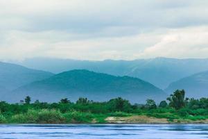 foresta, fiume, montagne e cielo foto