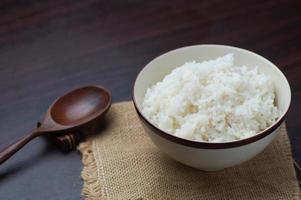 riso tailandese in una ciotola con un cucchiaio di legno sul tavolo