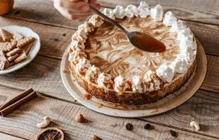 primo piano di una persona che mette la pioggia di caramello su una torta foto