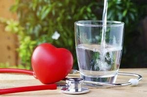 stetoscopio e cuore rosso con acqua su uno sfondo di legno