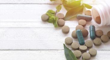 pillola compresse e capsule su fondo di legno bianco foto