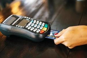 primo piano della donna che paga con carta di credito nella caffetteria