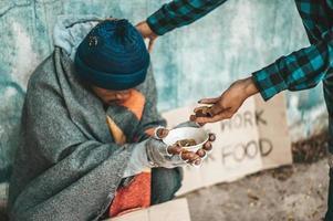 persona dà a un mendicante sul lato della strada foto