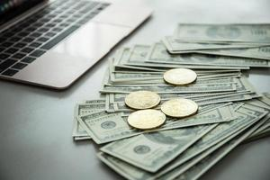 monete d'oro di bitcoin sulle banconote in dollari foto