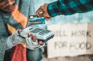 mendicanti seduti sotto il cavalcavia con una macchina per carte di credito e carte di credito foto