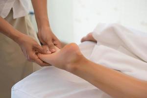 primo piano del massaggiatore che massaggia la gamba femminile al salone della stazione termale foto