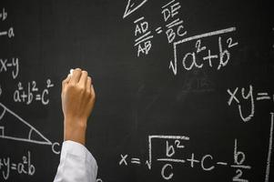 lo studente scrive la formula con il gesso bianco sulla lavagna foto