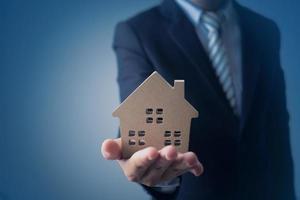 modello di casa uomo d'affari su sfondo blu scuro