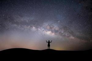 silhouette di una donna in cima a una collina con le stelle foto