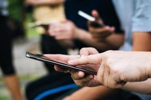 primo piano di amici che giocano insieme sugli smartphone foto