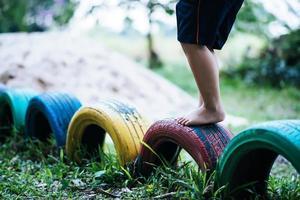 bambino che corre su pneumatici nel parco giochi foto