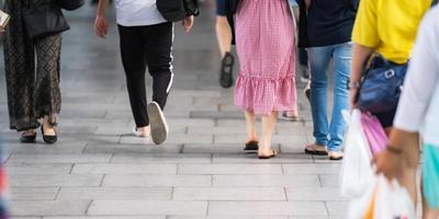 primo piano dei pedoni che camminano in città foto