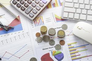 monete sulla scrivania con grafici e tastiera foto