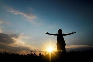 silhouette di una persona con le braccia aperte verso il cielo foto