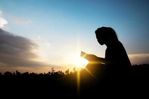 persona che legge in un campo al tramonto